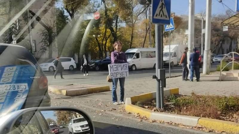 На Манаса стоит девушка с плакатом «Мэрия ворует». Фото