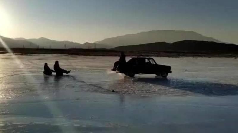 В заливе на Иссык-Куле санки привязывают к машине и катаются на замерзшем озере. Видео