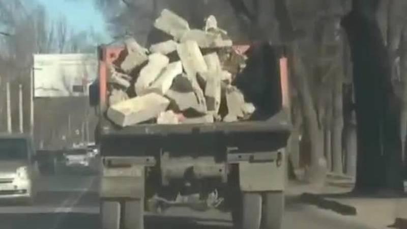 КамАЗ с открытым бортом везет бордюры. Видео