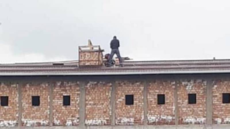 На крыше строящегося здания рабочий ходит без страховки. Фото
