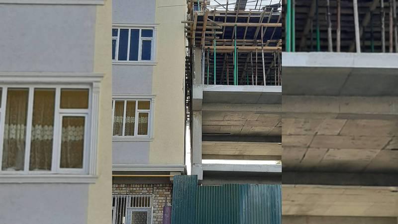 В городе Ош новый многоэтажный дом строится впритык к другому дому. Фото