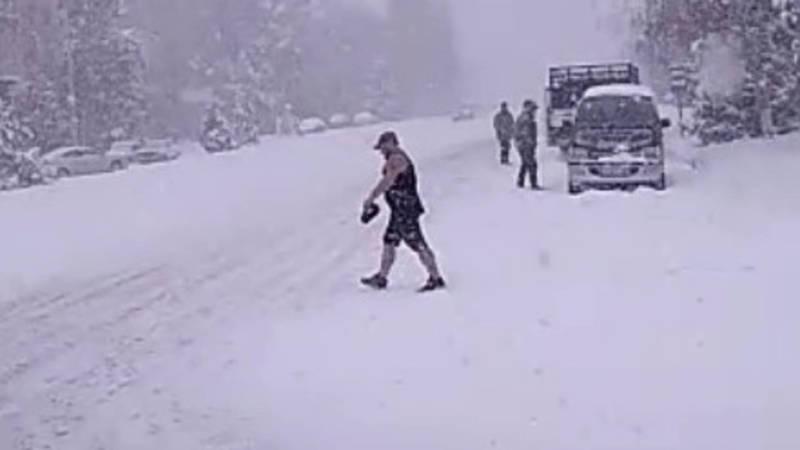 «Закаленный». В Караколе во время снегопада мужчина гуляет в майке и шортах. Видео