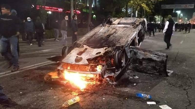 Соцсети: Возле ЦУМа во время столкновения митингующих с милицией сгорела патрульная машина