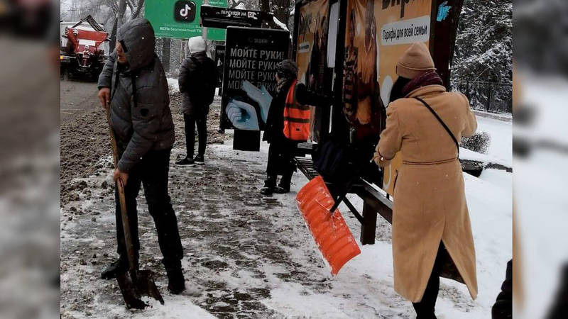 Прохожие помогают убирать снег работнице «Тазалыка». Фото