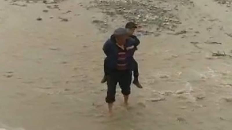 В Токтогульском районе жители на спинах переносят детей через реку. Видео