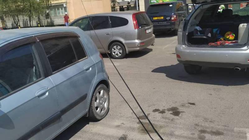 На ул. Масалиева возле дома №16 на парковке лежит электрический провод (фото)