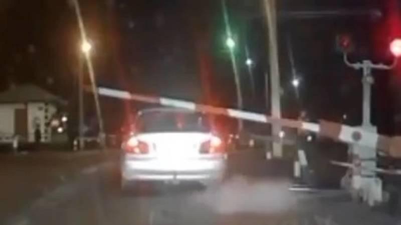 Машина проехала через железную дорогу на красный, повредив шлагбаум. Видео
