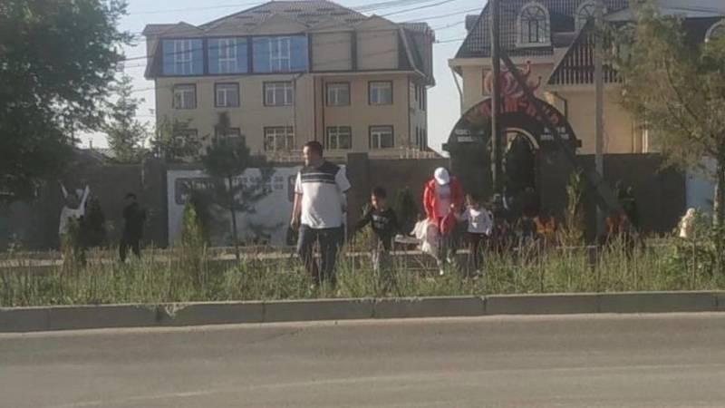 В Ак-Орго рядом со школой дети и родители ходят по газону