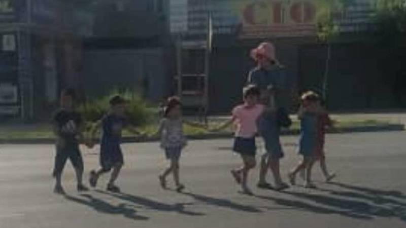 Воспитательница детсада с детьми переходит дорогу в неположенном месте