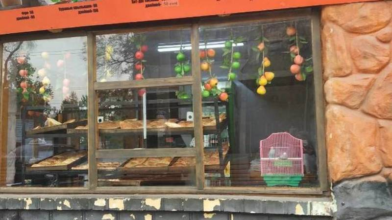 На витрине фаст-фуда на Пишпеке рядом с едой стоит клетка с птицами. Фото