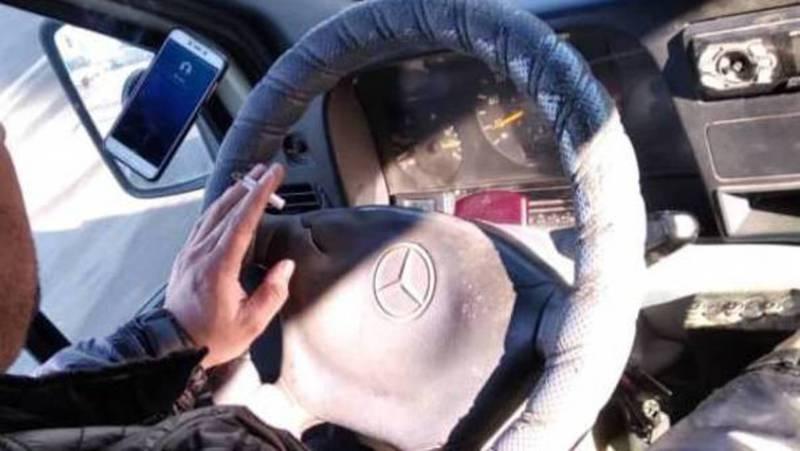 Водитель маршрутки №258 за рулем курит и разговаривает по телефону. Фото